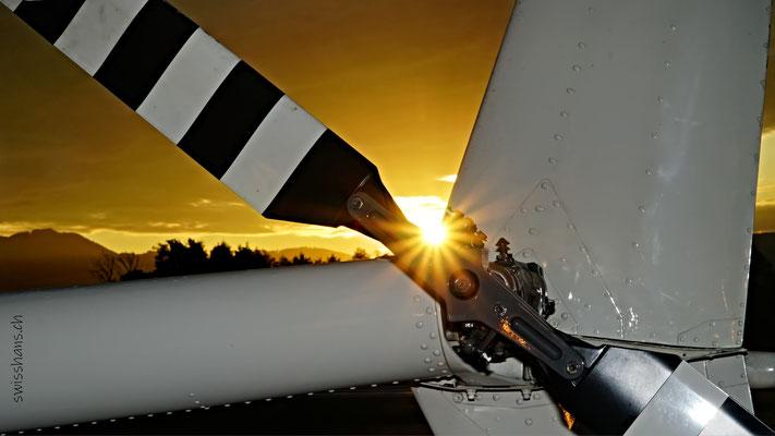 Sonnenuntergang. Sonne scheint durch den Heckrotor eines Helikopter beim Flugplatz Hohenems