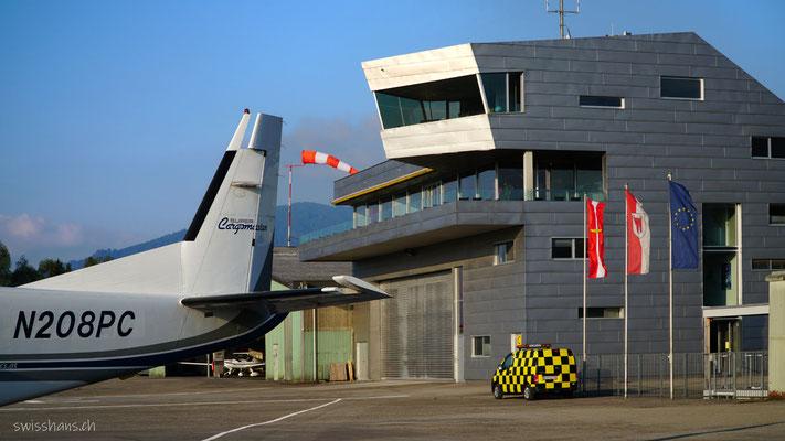 Flugplatzgebäude Flugplatz Hohenems mit Heck eines Flugzeuges.