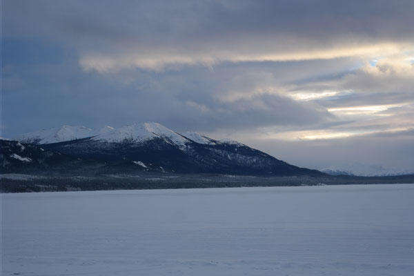 looking at jubilee mountain in the sunset over the frozen tagish lake
