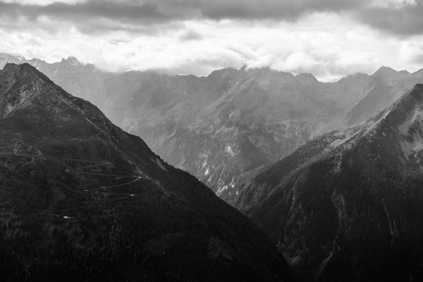 Black and white shot of the surrounding mountains from a lookout point.
