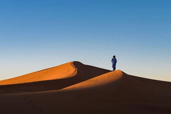 Ascension des dunes pendant le trek aux confins du Sahara