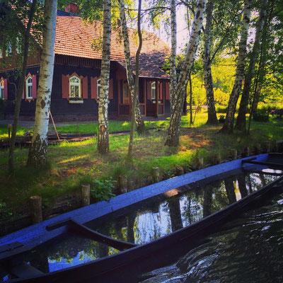 ein Kahn wässert am Grundstück in Kaupen im Spreewald