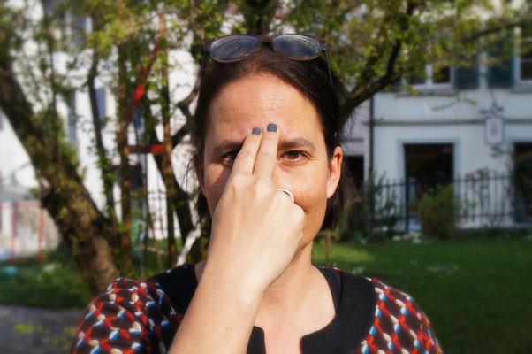 Zeige- und Mittelfinger auf Stirn legen