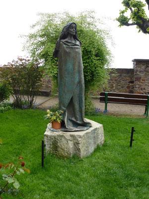 Eine Bronzeskulptur der Hildegard vor der Klostekirche
