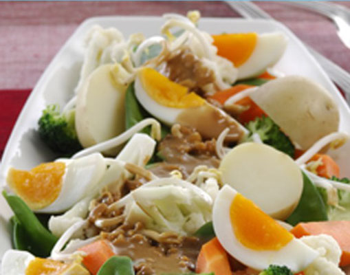 Variations of steamed mixed vegetables with peanut sauce.