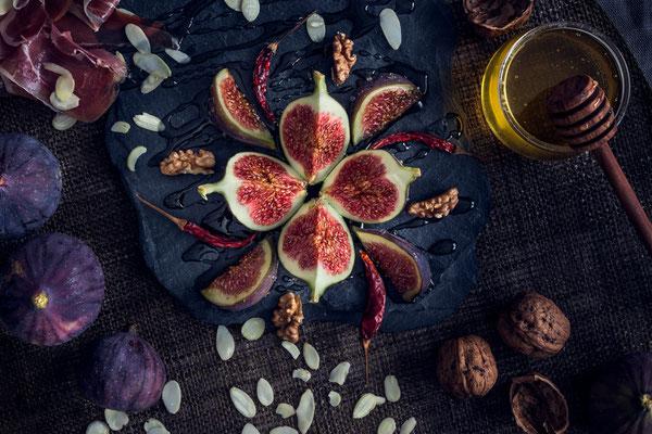 frische Feigen als Ornament auf Schieferplatte mit Honig und Nüssen von Tobias Gawrisch (Xplor Creativity)