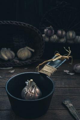 Knoblauch in gusseiserner Pfanne auf rustikalem Holztisch von Tobias Gawrisch (Xplor Creativity)