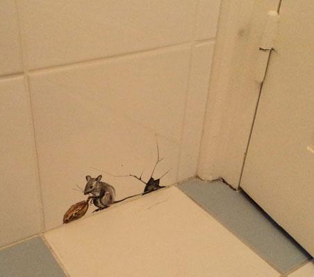 Une petite souris en trompe-l'œil cachée derrière la porte.