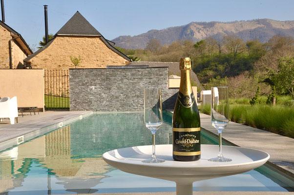 Mit einer Flasche Sekt im Vordergrund wirkt der Pool und die Ferienunterkunft gleich viel luxeriöser.