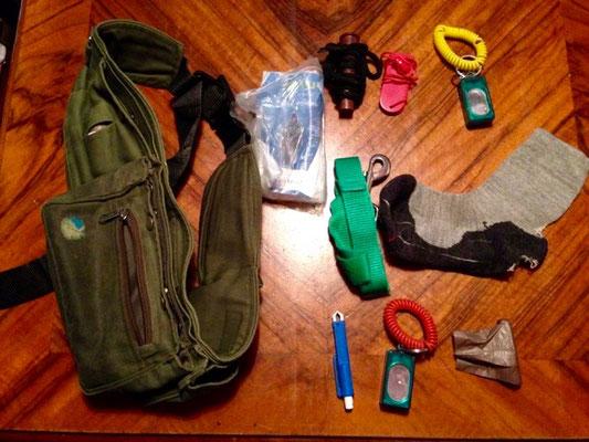Inhalt (von oben links nach rechts): Futtertube / verschiedene Leckerlis, Regenponcho, 2 Pfeifen, 1 Clicker, leichte, kurze (Not-)Leine, Socke zum Suchen, Finden, Zergeln, etc.,  Zeckenzange, 1 Ausleih-Clicker, Kotbeutel