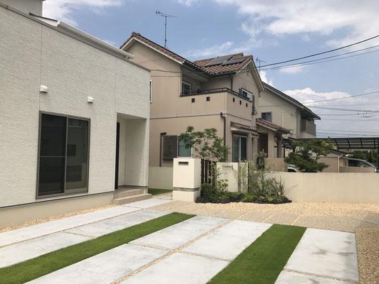 ご来客用の駐車スペースとして普段は解放されている玄関周りの空間に無機質なコンクリートだけでなく、芝生で緑のラインを追加することで柔らかい印象にしました。