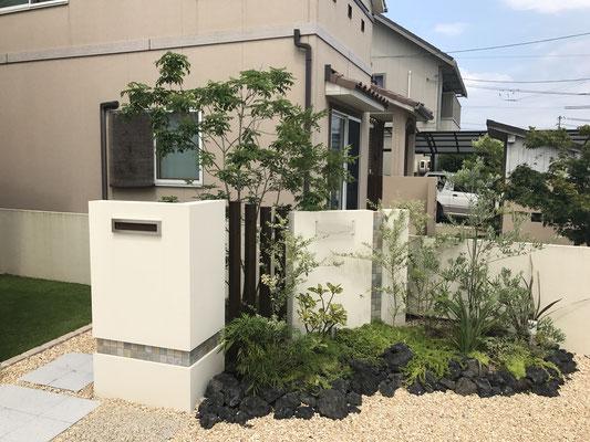 家の裏通路を隠す目的で設置した門壁にはポスト、表札を設置。アクセントに石タイルを張り、さらに植栽することで自然豊かな雰囲気になりました。