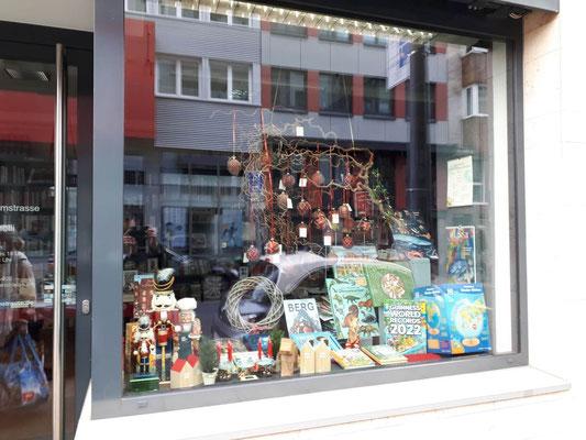 Buchhandlung Domstraße: kleines Schaufenster rechts, zur Domstraße hin, mit Weihnachtsbaumanhängern aus Glas und Kinderbüchern