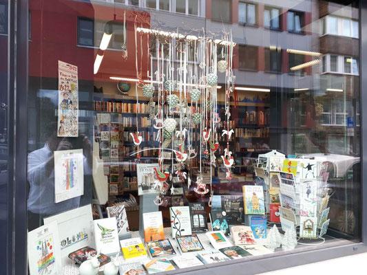 Buchhandlung Domstraße: kleines Schaufenster links, zur Domstraße hin, mit Weihnachtsbaumanhängern aus Glas, Büchern und Papeterie