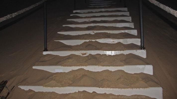 Installées il y a à peine quelques jours, les marches de l'escalier sont déjà pleines de sable ! Dur, dur...