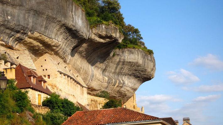 Die typischen Felsbauten hängen direkt über den Dächern vom Ort