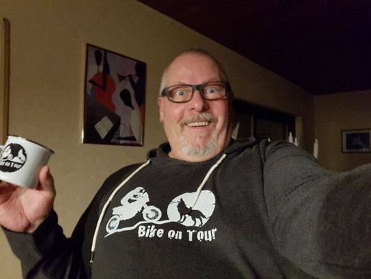 Jürgen mit seinem neuen Emaille-Häferl und Sweater aus dem Bike on Tour Shop