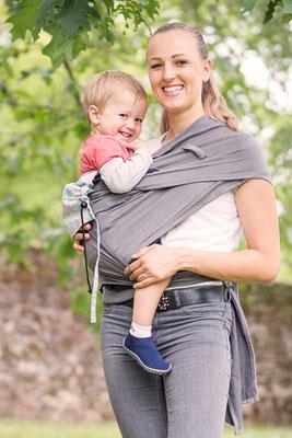Kind wird im Huckepack Wrap Tai auf der Hüfte getragen.