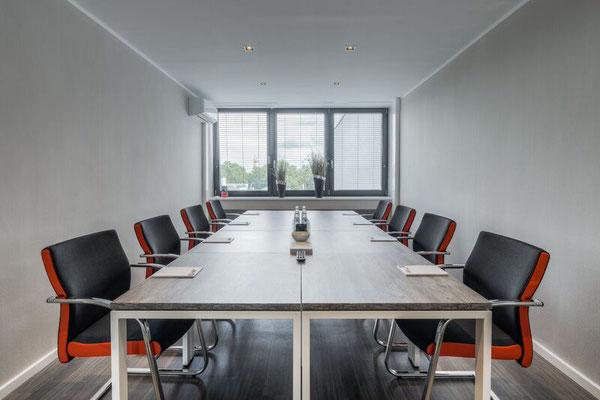 Konferenztischanlage mit schwebender Tischplatte in Eiche. Stühle mit Seitenstreifen - abgestimmt mit der Hausfarbe. Lieferbar in jeder anderen Abmessung, Ausführung und Farbkombination möglich.
