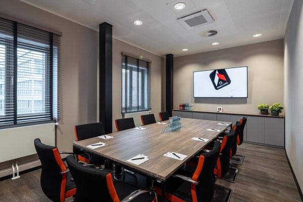 Besprechungsraum 10-12 Personen mit komfortabler Bestuhlung. Seitenstreifen in Firmenfarbe. Sideboard an  der Wandseite. - Lieferbar in jeder anderen Abmessung, Ausführung und Farbkombination möglich.