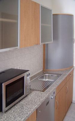 Küchenzeile mit Hängeschränken und Rundteil