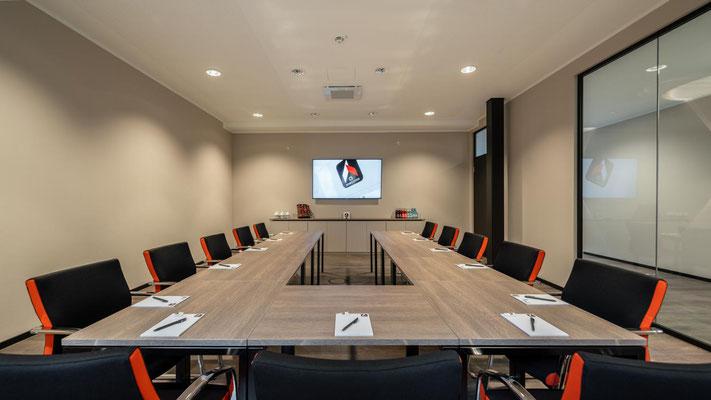 Besprechungsraum bis 20 Personen mit komfortabler Bestuhlung. Seitenstreifen in Firmenfarbe. Sideboard an  der Wandseite. - Lieferbar in jeder anderen Abmessung, Ausführung und Farbkombination möglich.