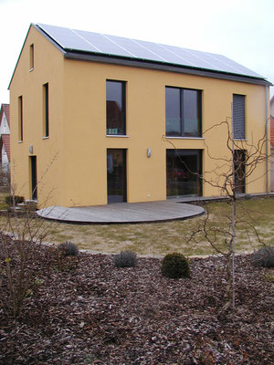 Passivhaus Kürnach- Südwest-Ansicht mit Süd-Terrasse und Außenanlagen