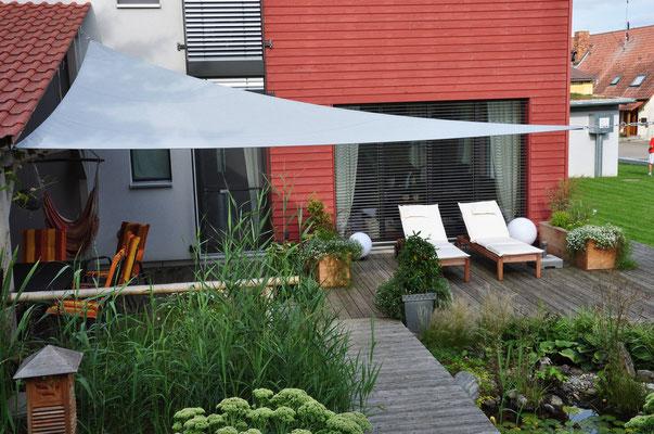 Plusenergie-/Passivhaus Willanzheim - West-Ansicht mit Blick auf Teich und Holzterrasse