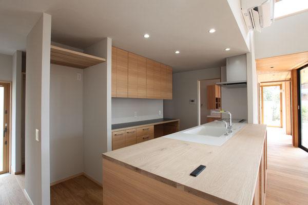 既製のシステムキッチンに同じ高さの製作家具でカウンターを造りつけてある、天板はナラ材
