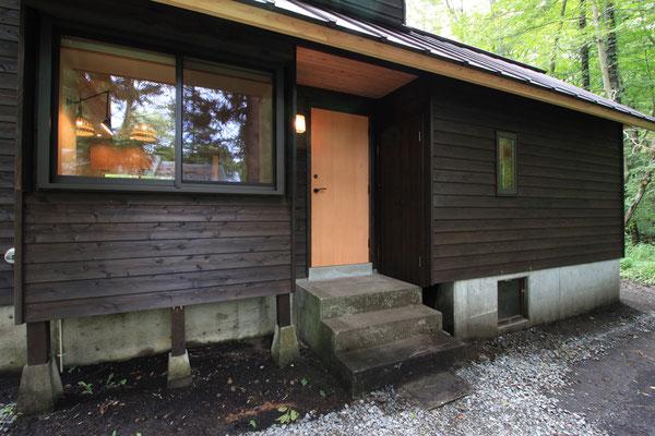 中央に玄関戸。その左がベンチ兼ベッドのある出窓、右が増築部分の寝室。