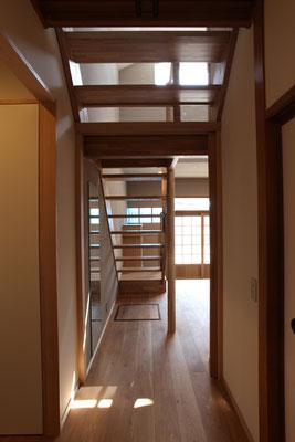 玄関を見返す 踊り場下には引戸を仕込んであり、熱環境を区切ることもできる 踊り場から上の蹴込みにはアクリル板はめ込んである