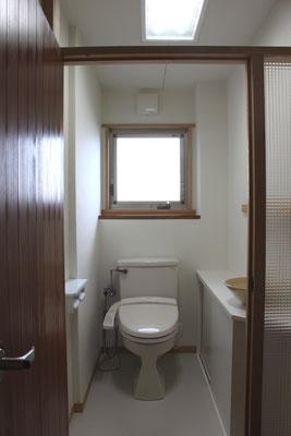 もともと洗面脱衣室であった部屋をトイレに改修した 入口の開き戸は既存浴室入口の木製建具を再利用した