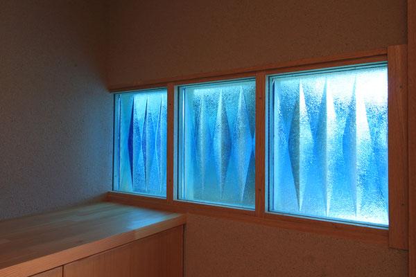 青い厚ガラスのアップ写真 内側にペアガラスを入れて断熱性能を確保