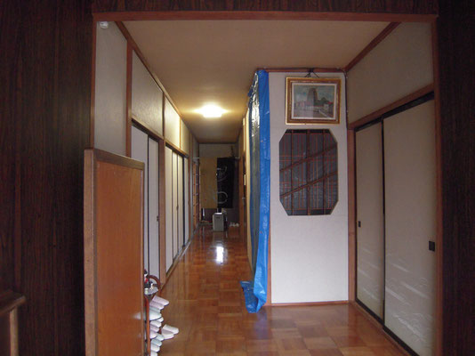 改修前の玄関から入った様子 昼間でも照明がないと暗い ブルーシートは2階への階段を撤去するため養生したところ