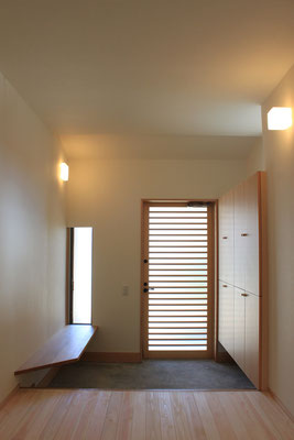 玄関内部 左手に靴の脱ぎはきに便利なようにベンチを設けた これは飾り棚としても機能する