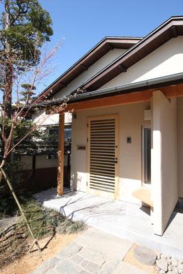玄関ポーチには石に沿ったところにベンチを設け、一呼吸おいてから左手に玄関戸がある