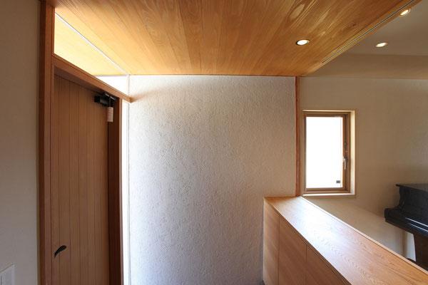 外部の左官壁仕上げと天井板が中に連続している