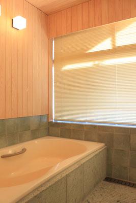 ブラインドを閉めると全体的に柔らかい空間になる  浴槽側面と床に使った十和田石が見える