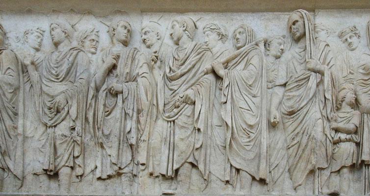 Priesterliche Prozession auf einem Relief der Ara Pacis, des Altars des Friedens des Augustus. In der Mitte die Flamines maiores, die Marspriester. Quelle: Ara pacis fregio lato ovest 2.JPG) [CC BY-SA 3.0 (http://creativecommons.org/lice