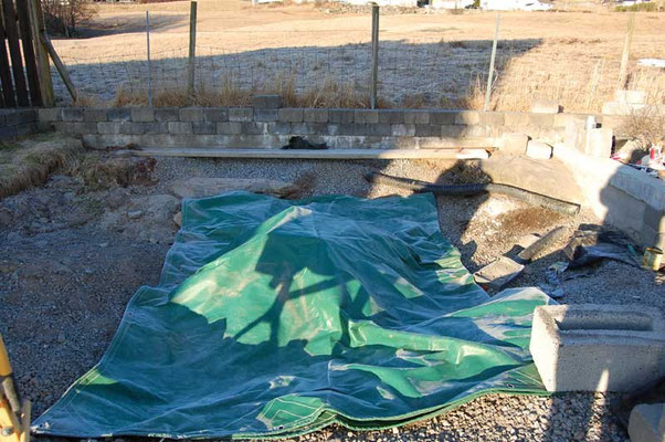 The completed base of the pier is covered with a tarpaulin to shield against night frost.