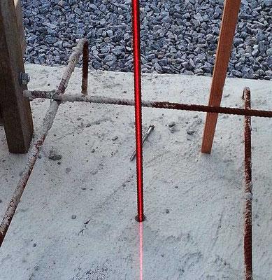 Laseren viser at jernstangen som markerer senteraksen er loddrett i et plan. For å gjøre stangen loddrett i alle plan må laserplanet roteres rundt senteraksen 90 grader.