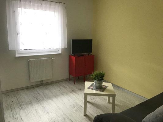 Gelbes Schlafzimmer mit Schlafcouch und TV