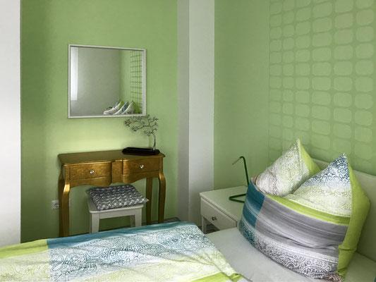 Grünes Schlafzimmer mit Doppelbett und TV