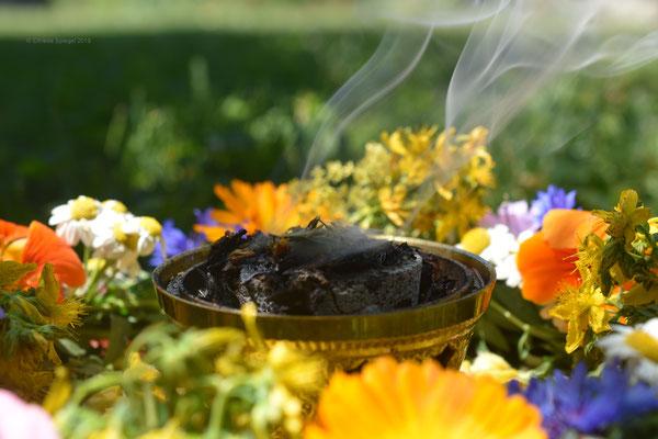 Räuchern zur Sommersonnenwende in dem Kreis aus Kräutern und Blüten