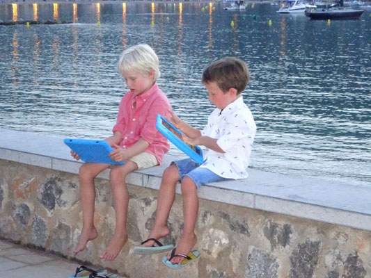 Little busy kids in the bay of Port de Soller