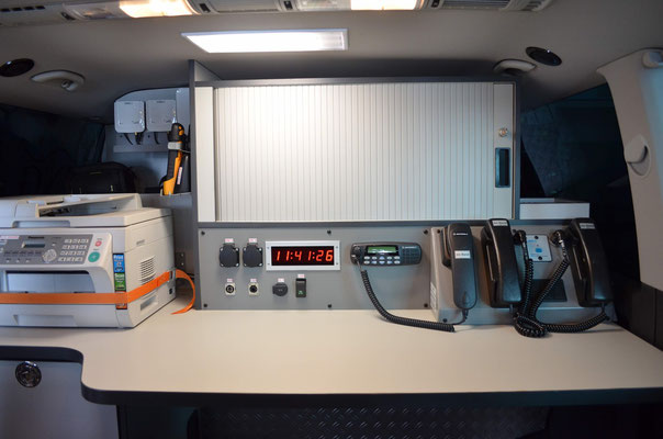 Arbeitsplatz mit div. Funkgeräten, Laptop, Internet und Telefone