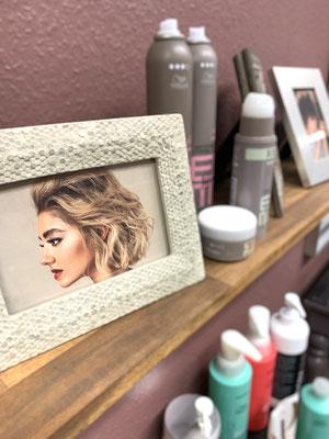 Bilderrahmen mit Frisurenbild und Stylingprodukten