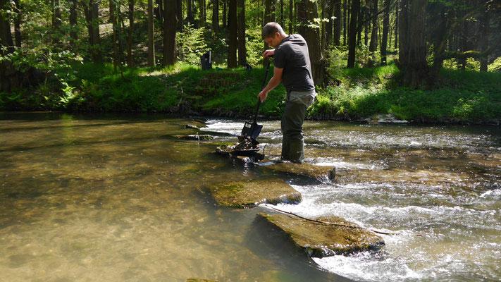 Mann mit Schaufel in Fluss