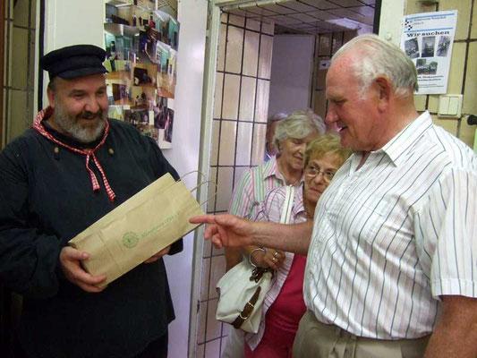 Fahrt-Organisator Hermann Röhling übergibt das Gastgeschenk