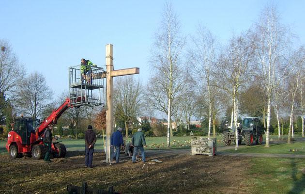 Mit Gurten wird das Kreuz provisorisch gehalten, bis das Betonfundament gegossen und ausgehärtet ist.